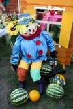 Η φωτεινή ραμμένη κούκλα κάθεται δίπλα σε ένα χρωματισμένο σπίτι και τα καρπούζια στοκ εικόνα με δικαίωμα ελεύθερης χρήσης