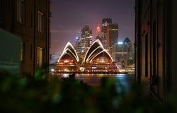 Η φωτισμένη Όπερα τη νύχτα κτήρια που πλαισιώνονται, σχεδιάζει τα καλολογικά στοιχεία, Στοκ φωτογραφία με δικαίωμα ελεύθερης χρήσης