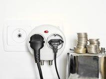 Η φωτογραφία έννοιας με τη piggy τράπεζα και τα νομίσματα που παρουσιάζουν το βούλωμα και κατανάλωση ηλεκτρικής ενέργειας σύνδεσα στοκ εικόνες