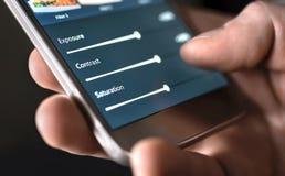 Η φωτογραφία εκδίδει με το κινητό τηλέφωνο και έξυπνο app Ολισθαίνοντες ρυθμιστές ρύθμισης ατόμων Έκδοση, χειρισμός, βελτίωση ή α στοκ εικόνες