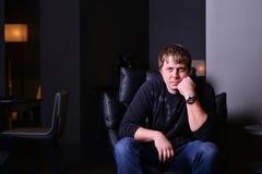 Η φωτογραφία εσωτερική του ατόμου κάθεται συλλογισμένα σε μια πολυθρόνα δέρματος Στοκ φωτογραφία με δικαίωμα ελεύθερης χρήσης