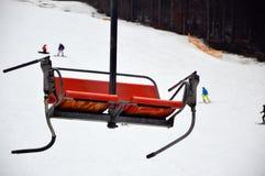 Η φωτογραφία κινηματογραφήσεων σε πρώτο πλάνο του κόκκινου κενού ανελκυστήρα καρεκλών κάθεται στο χιονώδες προς τα κάτω υπόβαθρο  Στοκ φωτογραφία με δικαίωμα ελεύθερης χρήσης