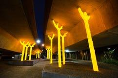 Η φωτογραφία νύχτας του έργου τέχνης ` επιδιώκει λάμψεις γλυπτών δέντρων ` φωτεινές και χρυσές κάτω από το σκυρόδεμα του αυτοκινη Στοκ Φωτογραφία