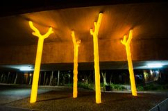 Η φωτογραφία νύχτας του έργου τέχνης ` επιδιώκει λάμψεις γλυπτών δέντρων ` φωτεινές και χρυσές κάτω από το σκυρόδεμα του αυτοκινη Στοκ φωτογραφία με δικαίωμα ελεύθερης χρήσης