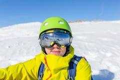 Η φωτογραφία της φίλαθλης φθοράς ατόμων καλύπτει και κράνος στο κλίμα του χιονώδους τοπίου βουνών Στοκ Εικόνες