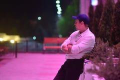 Η φωτογραφία του ατόμου Α σε ένα άσπρο πουκάμισο και μαύρα εσώρουχα στέκεται συλλογισμένα ενάντια στο αστικό τοπίο βραδιού Στοκ Εικόνα