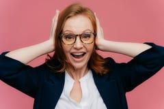 Η φωτογραφία του θετικού redhead εργαζομένου γραφείων θηλυκών κρατά τους φοίνικες στα αυτιά, εξετάζει ευτυχώς τη κάμερα, φορά την στοκ φωτογραφία