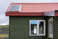 Η φωτογραφία του μικρού θερμοκηπίου άνεσης με την κόκκινη στέγη καρφιών και το ηλιακό πλαίσιο εγκαθιστούν στην κορυφή ενάντια στο στοκ εικόνες
