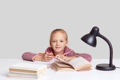 Η φωτογραφία του όμορφου μικρού μολυβιού λαβής παιδιών, εξετάζει τη κάμερα με τα μπλε μάτια, διαβάζει τα διαφορετικά βιβλία για τ στοκ εικόνες