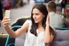 Η φωτογραφία του brunette που η νέα κυρία παίρνει selfie με το σύγχρονο τηλέφωνο κυττάρων, που ντύνεται στην άσπρη μπλούζα, κάνει στοκ φωτογραφία με δικαίωμα ελεύθερης χρήσης