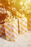Η φωτογραφία των κιβωτίων δώρων πολυτέλειας κάτω από το χριστουγεννιάτικο δέντρο, νέες εγχώριες διακοσμήσεις έτους, χρυσό τύλιγμα Στοκ Εικόνες