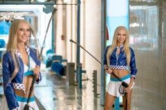 Η φωτογραφία των προκλητικών ξανθών προτύπων διαφημίζει το πλύσιμο αυτοκινήτων στοκ εικόνα