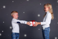 Η φωτογραφία Χριστουγέννων του μικρού αγοριού κάνει μια έκπληξη στο όμορφο κορίτσι, το άφησε να χιονίσει, δίνει ένα κιβώτιο-δώρο Στοκ Εικόνες
