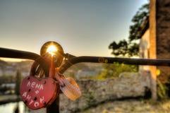 Η φωτογραφία HDR του ήλιου ηλιοβασιλέματος που λάμπει μέσω της αγάπης κλειδώνει την ένωση σε μια μεταλλική ράγα Στοκ Φωτογραφίες