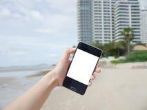 Η φωτογραφία Selfie με την άσπρη οθόνη smartphone για το σχέδιό σας και η θάλασσα στρώνουν με άμμο το υπόβαθρο Στοκ Εικόνα
