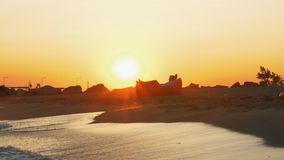 Η χαλάρωση ατόμων σε διογκώσιμο στην παραλία στο ηλιοβασίλεμα απόθεμα βίντεο