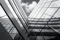 Η χαμηλή άποψη γωνίας του πετώντας αεροπλάνου πέρα από τη σύγχρονη αρχιτεκτονική χτίζει στοκ φωτογραφίες