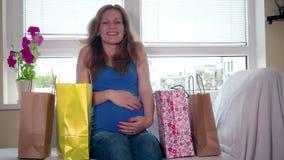 Η χαμογελώντας έγκυος γυναίκα κάθεται στον καναπέ με τις τσάντες αγορών και κτυπά μεγάλο tummy της απόθεμα βίντεο