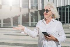 Η χαμογελώντας αποσυρμένη γυναίκα που ντύνεται στο άσπρο πουκάμισο στέκεται στην οδό πόλεων ακούοντας τη μουσική στα ακουστικά κα Στοκ Φωτογραφία