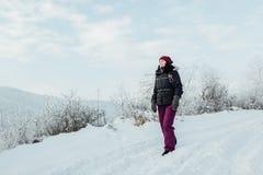 Η χαμογελώντας γυναίκα έντυσε θερμό απολαμβάνοντας έναν περίπατο στη χιονώδη χώρα Στοκ Φωτογραφία