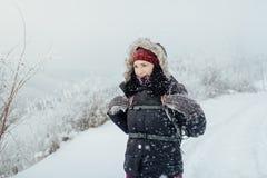 Η χαμογελώντας γυναίκα έντυσε θερμό απολαμβάνοντας έναν περίπατο στη χιονώδη χώρα Στοκ φωτογραφία με δικαίωμα ελεύθερης χρήσης
