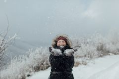 Η χαμογελώντας γυναίκα έντυσε θερμό απολαμβάνοντας μια χιονώδη ημέρα έξω Στοκ Εικόνες