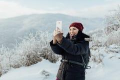 Η χαμογελώντας γυναίκα έντυσε θερμό παίρνοντας ένα selfie κατά τη διάρκεια ενός χειμερινού περιπάτου Στοκ Εικόνα