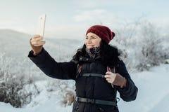 Η χαμογελώντας γυναίκα έντυσε θερμό παίρνοντας ένα selfie σε μια χιονώδη χώρα Στοκ εικόνα με δικαίωμα ελεύθερης χρήσης