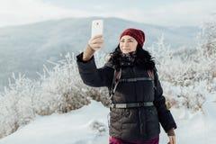 Η χαμογελώντας γυναίκα έντυσε θερμό παίρνοντας ένα selfie σε μια χιονώδη χώρα Στοκ φωτογραφία με δικαίωμα ελεύθερης χρήσης