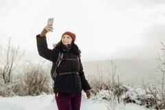 Η χαμογελώντας γυναίκα έντυσε θερμό παίρνοντας ένα selfie σε μια χιονώδη χώρα Στοκ Εικόνες