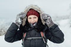 Η χαμογελώντας γυναίκα έντυσε τη θερμή εκμετάλλευση η κουκούλα της με τα χιονώδη γάντια Στοκ φωτογραφίες με δικαίωμα ελεύθερης χρήσης