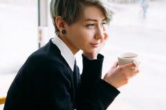 Η χαμογελώντας γυναίκα απολαμβάνει την απόλαυση φλυτζανιών λαβής καφέδων ελεύθερου χρόνου Στοκ Φωτογραφίες