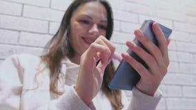 Η χαμογελώντας γυναίκα δακτυλογραφεί ένα μήνυμα στην κινητές τηλεφωνικές συνεδρίαση και την αναμονή κάποιος στον καφέ φιλμ μικρού μήκους