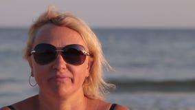 Η χαμογελώντας γυναίκα εξετάζει τη κάμερα και βάζει στα γυαλιά στα πλαίσια των κυμάτων θάλασσας φιλμ μικρού μήκους