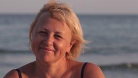 Η χαμογελώντας γυναίκα εξετάζει τη κάμερα και βάζει στα γυαλιά στα πλαίσια των κυμάτων θάλασσας απόθεμα βίντεο
