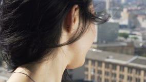Η χαμογελώντας γυναίκα εξετάζει υπόβαθρο κτηρίων πόλεων το σε αργή κίνηση, αστικό άνωθεν απόθεμα βίντεο