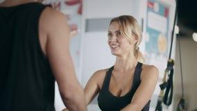 Η χαμογελώντας γυναίκα ικανότητας που κρατά τον προσωπικό εκπαιδευτή παραδίδει τη λέσχη γυμναστικής απόθεμα βίντεο