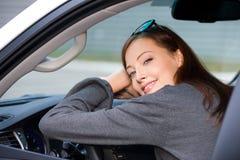 Η χαμογελώντας γυναίκα κάθεται στο νέο αυτοκίνητο Στοκ φωτογραφίες με δικαίωμα ελεύθερης χρήσης