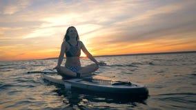 Η χαμογελώντας γυναίκα σε έναν λωτό θέτει παρασύρει στο paddleboard της καρπός ρολογιών χαλάρωσης τσεπών χεριών έννοιας απόθεμα βίντεο
