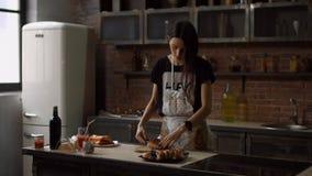 Η χαμογελώντας γυναίκα στην ποδιά βάζει τα κομμάτια της πίτας στο πιάτο απόθεμα βίντεο