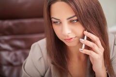 Η χαμογελώντας γυναίκα στη συζήτηση γραφείων στο τηλέφωνο και χρησιμοποιεί τον υπολογιστή s Στοκ φωτογραφία με δικαίωμα ελεύθερης χρήσης