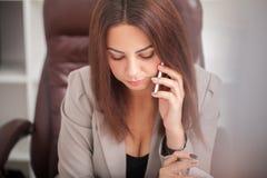 Η χαμογελώντας γυναίκα στη συζήτηση γραφείων στο τηλέφωνο και χρησιμοποιεί τον υπολογιστή s Στοκ Εικόνες