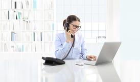 Η χαμογελώντας γυναίκα στη συζήτηση γραφείων στο τηλέφωνο και χρησιμοποιεί τον υπολογιστή s Στοκ Φωτογραφία