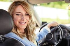 Η χαμογελώντας γυναίκα στο αυτοκίνητο ξανακοιτάζει μια θερινή ημέρα Στοκ Φωτογραφία