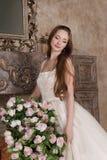 74c43c83c3fc Η χαμογελώντας γυναίκα στο μακρύ φόρεμα κρατά το καλάθι των λουλουδιών στοκ  εικόνες