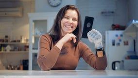 Η χαμογελώντας κυρία με ένα προσθετικό χέρι έχει μια τηλεοπτική κλήση απόθεμα βίντεο