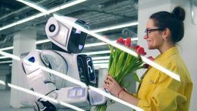 Η χαμογελώντας κυρία παίρνει τα λουλούδια και το αγκάλιασμα ενός cyborg απόθεμα βίντεο
