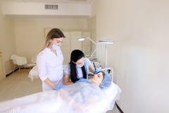 Η χαμογελώντας κυρία που παίρνει επαγγελματικό μόνιμο αποτελεί από το cosmetologist και τη νοσοκόμα στοκ εικόνες με δικαίωμα ελεύθερης χρήσης