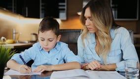 Η χαμογελώντας μητέρα που βοηθά το γιο του που κάνει την εργασία, υπαγορεύει το κείμενο για να σας βοηθήσει να γράψετε τη συνεδρί απόθεμα βίντεο