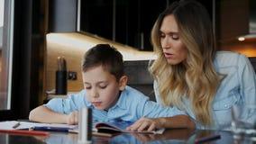 Η χαμογελώντας μητέρα που βοηθά το γιο του που κάνει την εργασία, υπαγορεύει το κείμενο για να σας βοηθήσει να γράψετε τη συνεδρί φιλμ μικρού μήκους